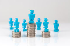 Male and female figurines standing on top of coin piles Royalty Free Stock Photo
