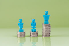 Male and female figurines standing on top of coins Stock Image