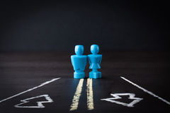 Male and female figurines on two way road Royalty Free Stock Photography
