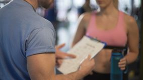 Male and female fitness trainers discussing their work schedules in gym. Stock footage stock video