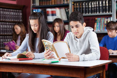 Male And Female Friend Studying In Library. Male and female friends studying at table with classmates in library Stock Photography
