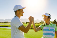 Male and female friends giving high-five at golf course Royalty Free Stock Photography