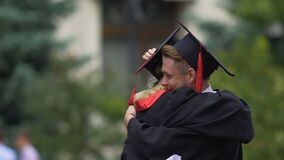 Male and female friends hugging, holding higher education diplomas in hands. Stock footage stock video