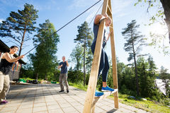 Male And Female Friends Pulling Ropes To Balance Woman On Wooden. Multiethnic male and female friends pulling ropes to balance women on wooden structure at patio Royalty Free Stock Images