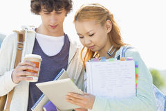 Male and female friends using digital tablet at college campus Stock Image