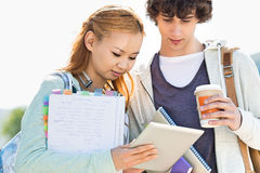 Male and female friends using digital tablet at college campus Stock Photos