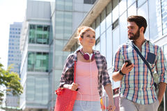 Male and female friends walking outside office building on sunny day Royalty Free Stock Images