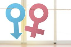 Male and female gender symbol hanging on the rope. Equality gender concept stock images