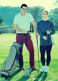 Male and female golfers ready for team play at golf course Royalty Free Stock Images
