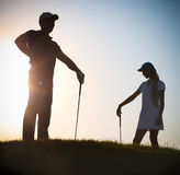 Male and female golfers at sunset Royalty Free Stock Photo
