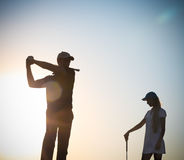 Male and female golfers at sunset Stock Photo