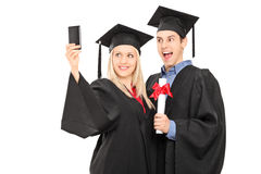 Male and female graduate students taking a selfie. Isolated on white background Stock Photography