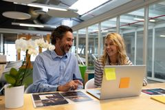 Male and female graphic designers discussing over laptop at desk. Side view of Caucasian male and female graphic designers discussing over laptop at desk in stock photography