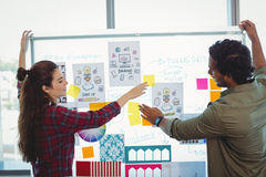 Male and female graphic designers discussing over sticky notes royalty free stock photos