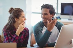 Male and female graphic designers interacting with each other at desk Royalty Free Stock Images
