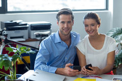 Male and female graphic designers using mobile phone. In office Stock Image