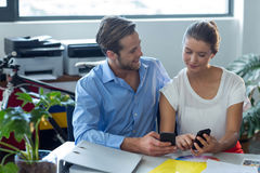 Male and female graphic designers using mobile phone. In office Stock Photos