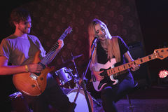 Male and female guitarist performing in nightclub Stock Images