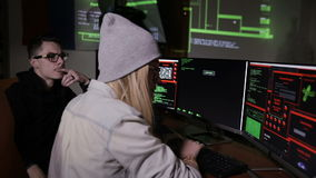 Male and female hackers working on computers with data code on display screens in a dark room. HD stock footage