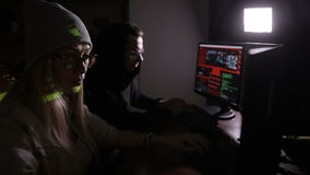 Male and female hackers working on computers with data code on display screens in a dark room. HD stock video footage