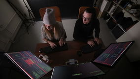 Male and female hackers working on computers with data code on display screens in a dark room. HD stock video