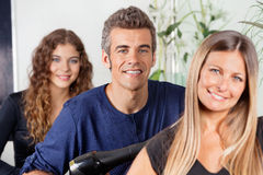 Male And Female Hairstylists At Salon stock photo