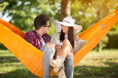 Male and female in hammock speaking Royalty Free Stock Images