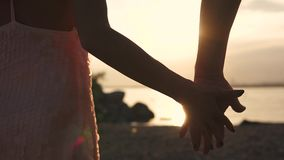 Male and female hand close-up against the setting sun. Gentle touch of two lovers. Love, romance, friendship. A touch of male and female hands against the sunset stock video footage