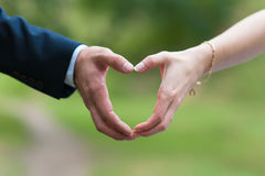 Male and female hand connected in form of heart. Hand of the bride and groom are connected in the form of heart. The groom in a suit. Caucasian couple outdoors Stock Images