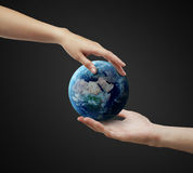 Male and female hand holding earth. Royalty Free Stock Images