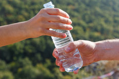 Male and female hand holding plastic water bottle closeup outdoors. Male and female hand holding plastic bottle of water closeup on forest background Stock Images