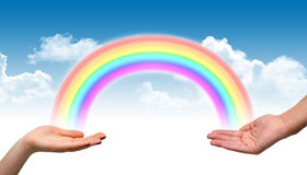 Male and female hand holding a rainbow Stock Image