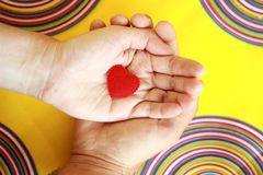 Two hands with red heart on yellow background royalty free stock images