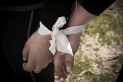 Two hands tied by a ribbon royalty free stock photography