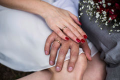 Male and female hand with a wedding ring, a female hand with red nails Royalty Free Stock Photos