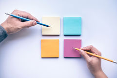 Male and female hand writing on notepaper color background. stock photo