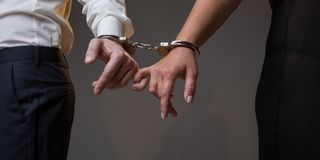 Male and female hands chained by handcuffs stock images