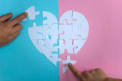 Male and female hands collect puzzle heart. On pink and blue background royalty free stock images