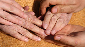Male and female hands comforting a old pair of hands outdoor. Royalty Free Stock Photo