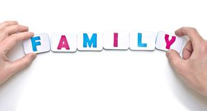 Male and female hands creating word family with magnetic letters Royalty Free Stock Images