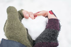 Male and female hands in gloves holding a snow shaped heart. Boy's and girl's hand holding a heart made of snow Royalty Free Stock Photos