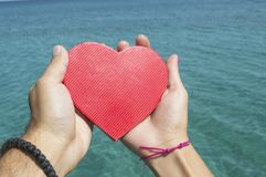 Male and female hands holding a heart above the sea water. Male and female hands holding a red paper heart above the sea water royalty free stock photography