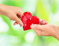 Male and female hands holding red heart Royalty Free Stock Photo