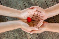 Male and female hands holding red heart on wooden background.  stock image