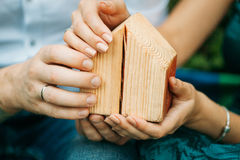 The male and female hands holding a small house. The male and female hands holding a small wooden decorative house Stock Photography