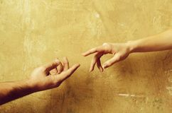 Male and female hands reaching to each other. Expressions and gesture, male and female hands reaching to each other on abstract cement wall on beige background royalty free stock photos