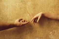 Male and female hands reaching to each other. On abstract cement wall on beige background. Help and care stock photos