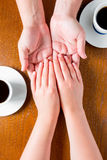 Male and female hands on the table with cups Stock Photo