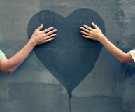 Male and female hands touching painted heart. On concrete wall royalty free stock photography