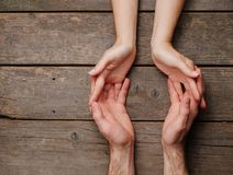 Male and female hands on wooden background with copy space royalty free stock photography